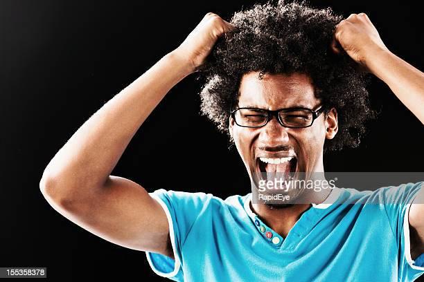 Wütend junger Mann reißt seine Haare gegen Schwarz