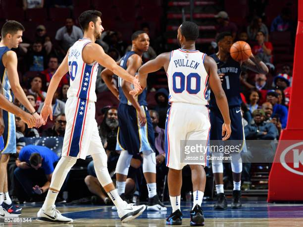 Furkan Korkmaz and Jacob Pullen of the Philadelphia 76ers high five each other during the game against the Memphis Grizzlies during a preseason game...