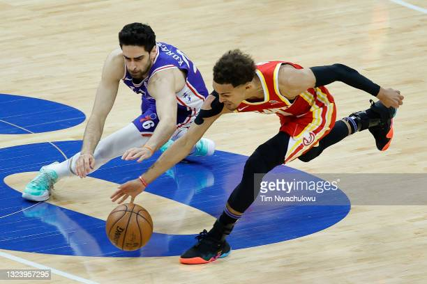 Furkan Korkmaz of the Philadelphia 76ers and Trae Young of the Atlanta Hawks reach for a loose ball during the third quarter during Game Five of the...