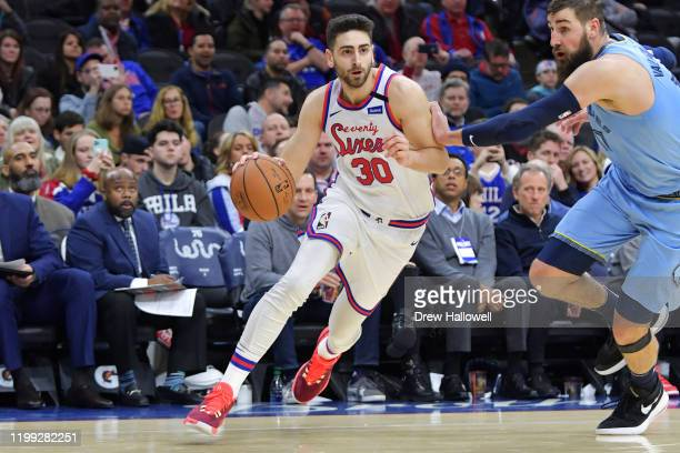 Furkan Korkmaz of the Philadelphia 76ers drives on Jonas Valanciunas of the Memphis Grizzlies in the second half at Wells Fargo Center on February 7...