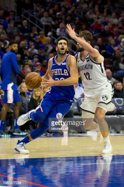 Furkan Korkmaz of the Philadelphia 76ers drives to the basket against Joe Harris of the Brooklyn Nets at the Wells Fargo Center on December 12 2018...