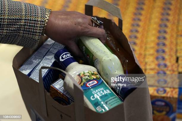 A furloughed federal worker bags free food at a popup store of Kraft Heinz January 17 2019 in Washington DC Kraft Heinz opened a store to distribute...