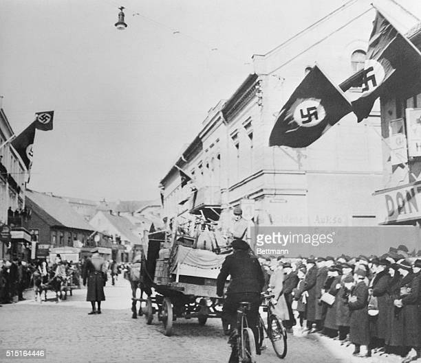 Furniture and other possessions of a Jewish family on a horsedrawn cart passing beneath the swastika flag during the flight from Memel German crowds...