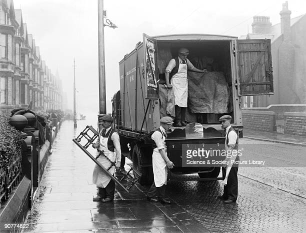Furniture being unloaded from a van to a house on a wet day It was common to use the railways when moving house Furniture was loaded into a container...