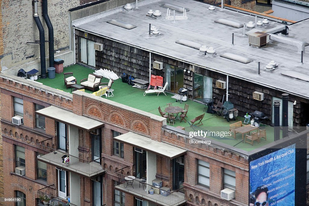Furniture Sits On The Rooftop Deck Of An Apartment Building
