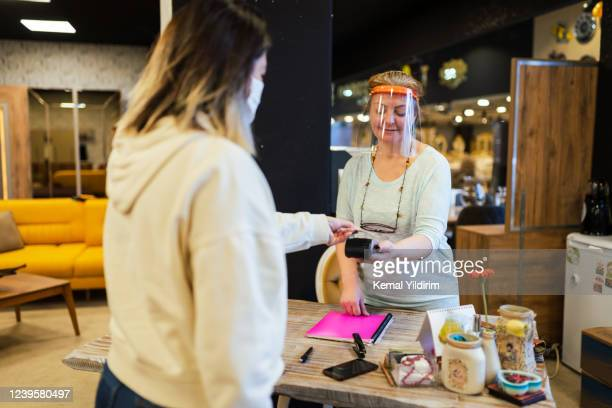 furniture store owner receives contactless payment due to social distancing - new normal concept stock pictures, royalty-free photos & images