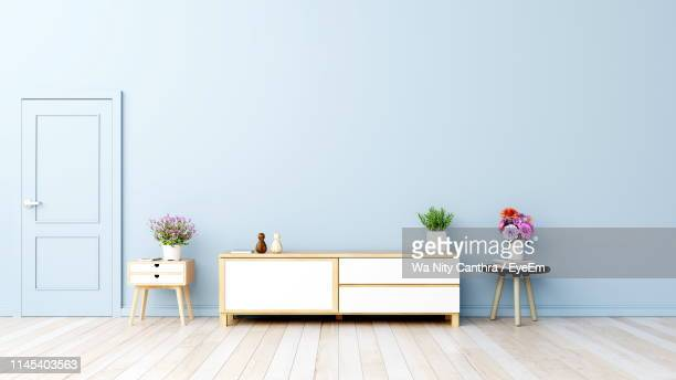 furniture with decorations arranged by wall at home - neat stock pictures, royalty-free photos & images