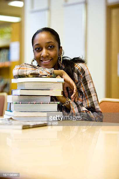 further education: a friendly female student with books - girl mound stock pictures, royalty-free photos & images