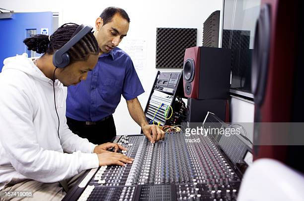 further education: teacher and pupil on recording studio mixing desk