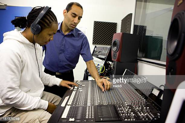 further education: teacher demonstrating music technology equipment to a pupil