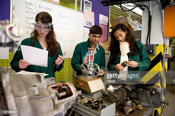 Estudiantes de ingeniería mecánica adolescente estudiando en el taller