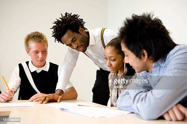 further education: teenage students working with their teacher in class
