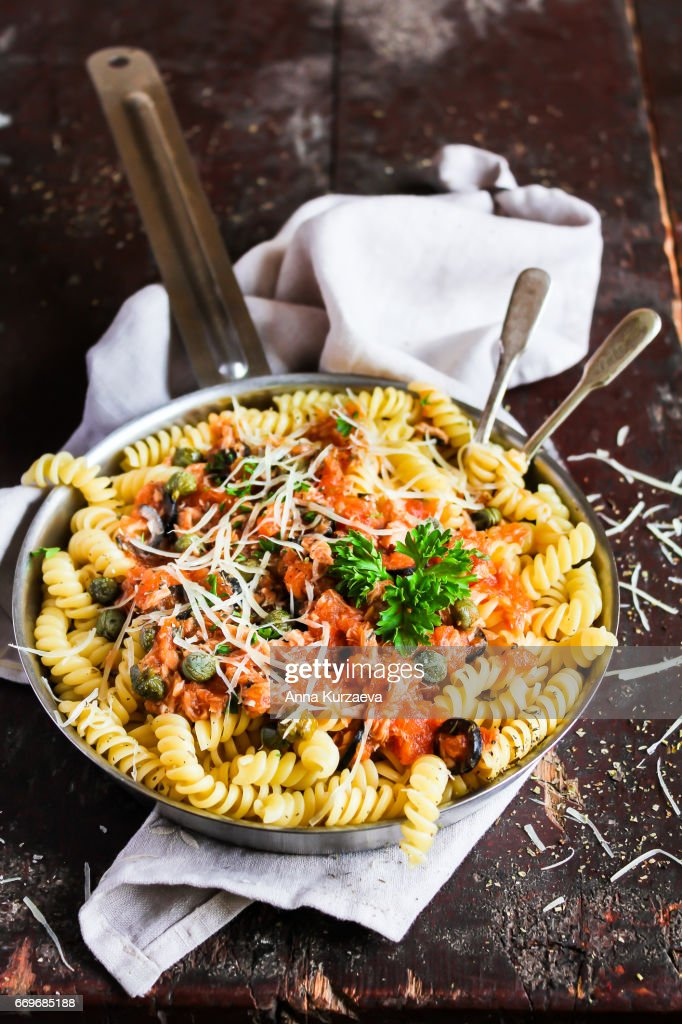 Fusilli pasta dish with tuna fish, tomato sauce, capers, black olives and parmesan cheese in a cooking pan on a wooden table, selective focus : Stock Photo