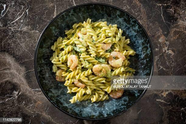 fusilli with pesto sauce - pesto stock pictures, royalty-free photos & images