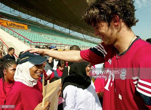 Fussball 1 Bundesliga 03/04 Dubai FC Bayern Muenchen / Training Michael BALLACK verschenkt FanArtikel an behinderte Kinder 130104