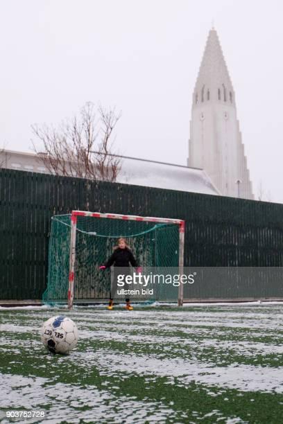 Fussball spielende Kinder am ersten Weihnachtsfeiertag unterhalb der Hallgrimskirkja in Reykjavik