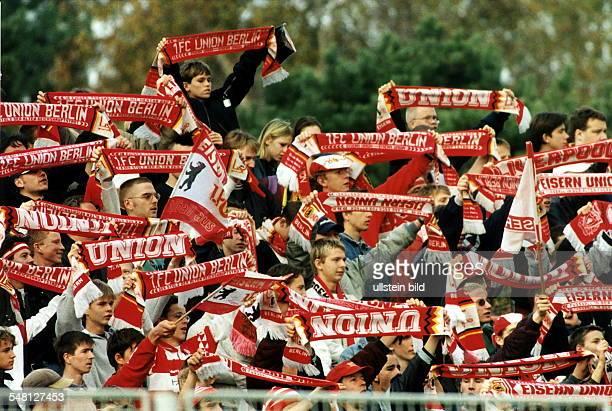 Fussballfans vom 1.FC Union Berlin schwenken auf der Tribüne Schals und Fahnen - 1997