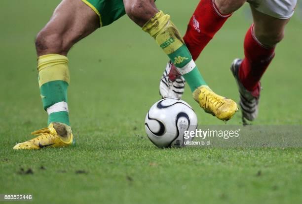 Fussballspieler in Nike und AdidasSchuhen im Zweikampf um den AdidasBall 'Teamgeist'