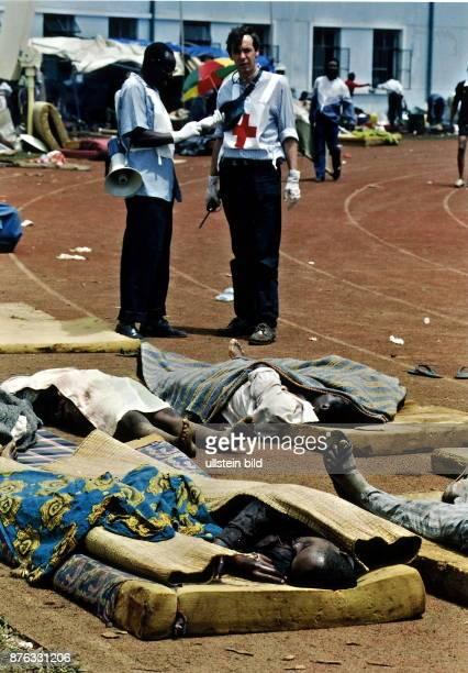 Tutsi Opfer eines Granatangriffs auf Matratzen im Hintergrund Helfer des Roten Kreuz Mai 1994