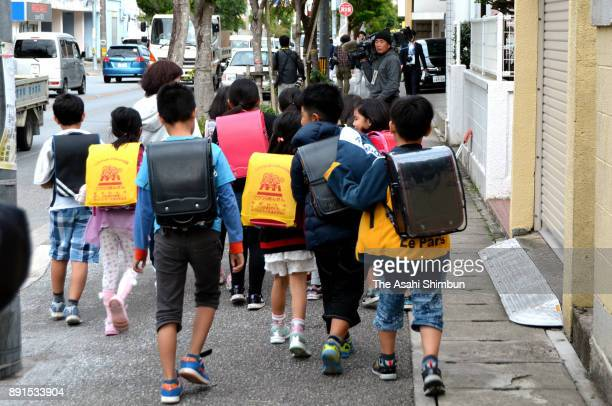 Futenma Daini Elementary School pupils return their home after a window frame of a US helicopter fell on the ground on December 13 2017 in Ginowan...