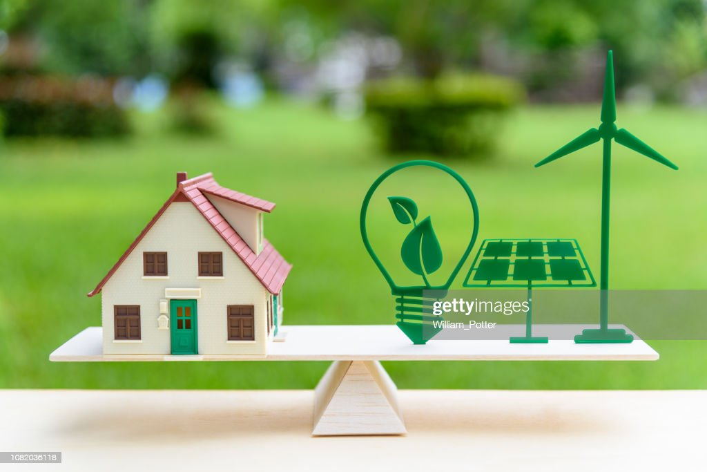 Future clean / renewable or alternative energy for modern living concept : House model, light bulb with green leaf, solar panel, wind mill on wood balance scale, depicts the awareness of environment. : Stock Photo