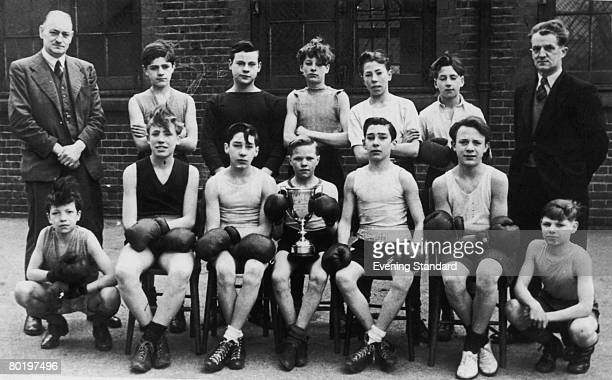 Future London gangsters the Kray twins Ronnie and Reggie with their youth boxing team and a trophy circa 1946