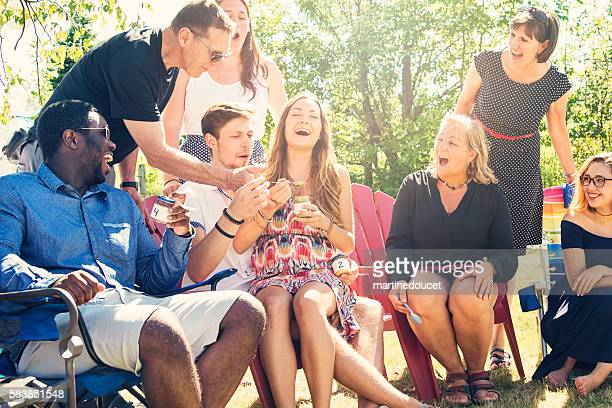 Future parents tasting baby food at shower party in summer.