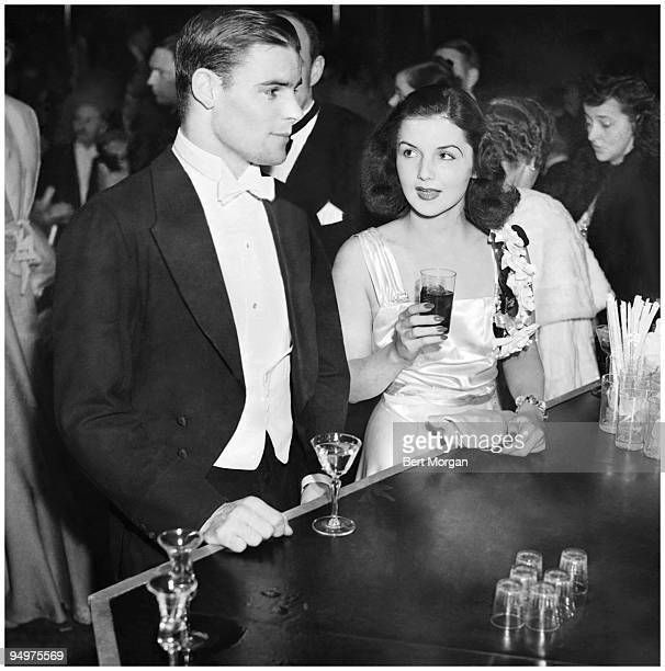 Future US Representative from NY Garrow T Geer Jr and his date Brenda Frazier the most famous debuntante in the world in formal wear getting drinks...