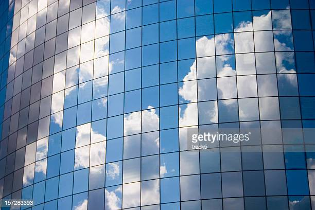 Futuristic abstract business background with reflected blue skies and clouds
