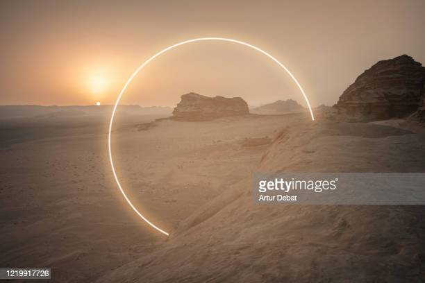 futuristic circle made with neon lights in the desert landscape. - modern rock stock pictures, royalty-free photos & images