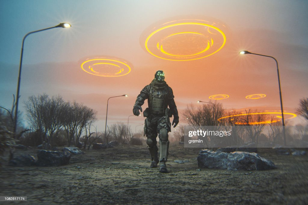 Futuristic cyborg walking in desert with flying UFOs : Stock Photo