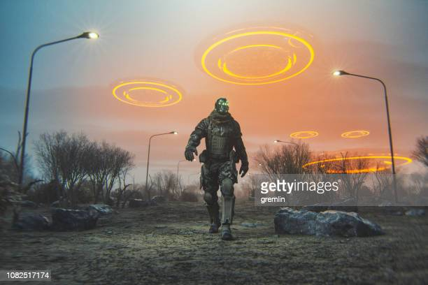 futuristic cyborg walking in desert with flying ufos - military invasion stock pictures, royalty-free photos & images