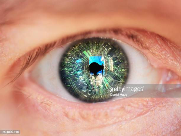 a futuristic electronic eye depicting the advances in medical technology embedded in the human form - artificial intelligence stock pictures, royalty-free photos & images