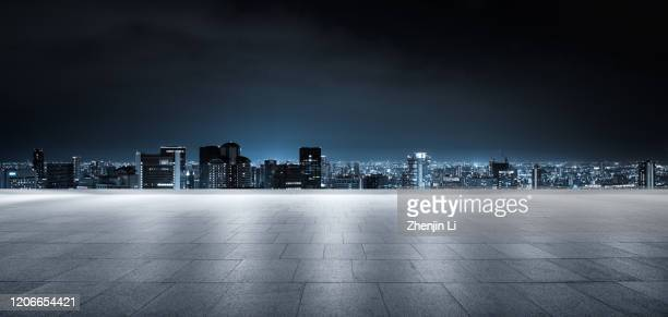 futuristic empty parking ground with urban city skyline high res panorama - city night stock pictures, royalty-free photos & images