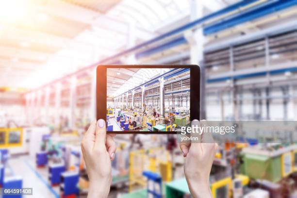 Futuristic factory & hands holding tablet