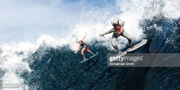 futuristic female surfers using hover boards to surf down large waves - hoverboard stock pictures, royalty-free photos & images