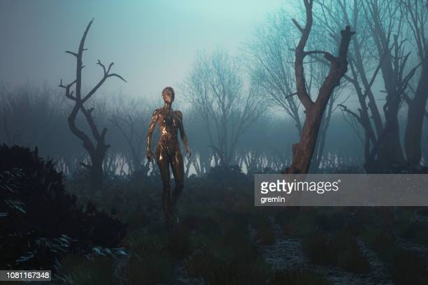 futuristic golden cyborg walking in the forest at night - fictional character stock pictures, royalty-free photos & images