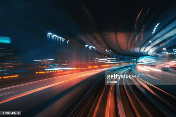 futuristic high speed light tail with night city background - speed stock pictures, royalty-free photos & images