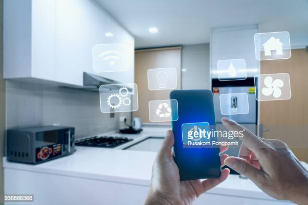futuristic interface of smart home automation assistant on a virtual screen and a user touching a button - house icon stock pictures, royalty-free photos & images