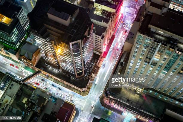 futuristic lights of the streets of a busy city at night glow vividly - aerial view stock pictures, royalty-free photos & images
