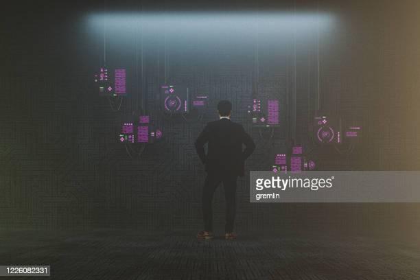 homme futuriste devant des moniteurs d'ordinateur suspendus - écran numérique photos et images de collection