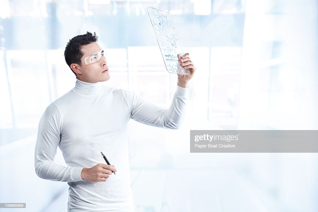 Futuristic man looking at a board with DNA codes : Stock Photo