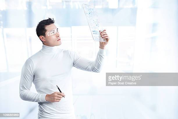 Futuristic man looking at a board with DNA codes