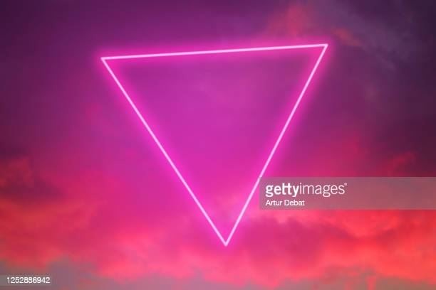 futuristic neon triangle in the burning sky with stunning pink colors. - triangle shape stock pictures, royalty-free photos & images