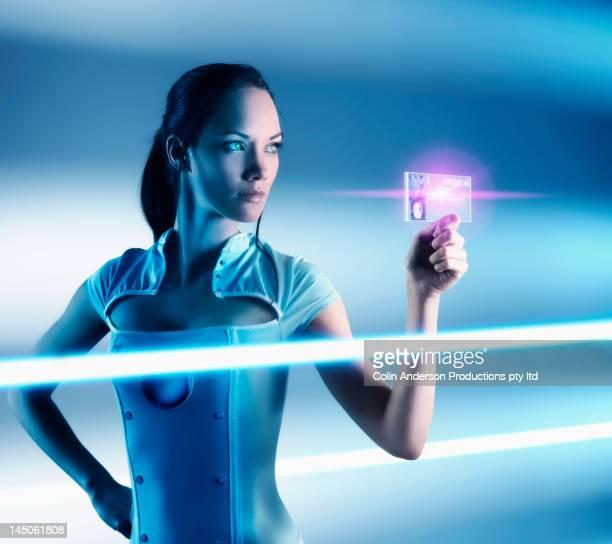 Futuristic Pacific Islander woman holding glowing screen