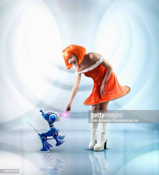 futuristic pacific islander woman playing with robot dog - orange dress stock pictures, royalty-free photos & images