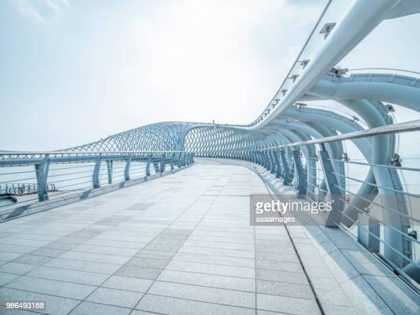 futuristic pedestrian footbridge against sky - man made structure stock pictures, royalty-free photos & images