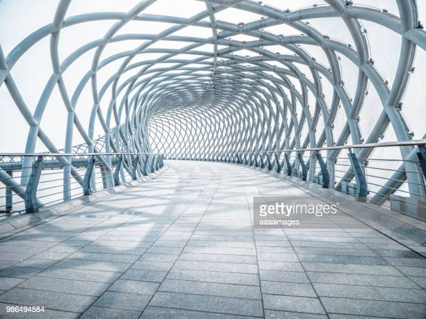 futuristic pedestrian footbridge against sky - architecture stock pictures, royalty-free photos & images