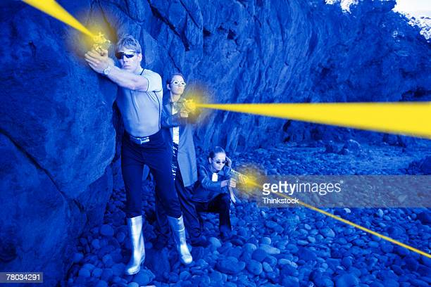 futuristic people shooting laser guns from rocks - tinted sunglasses stock pictures, royalty-free photos & images