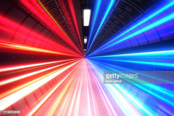 futuristic picture of colorful light trails going fast inside tunnel. - igniting stock pictures, royalty-free photos & images